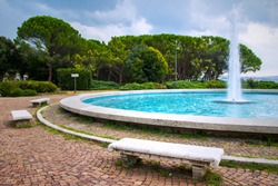 Pine trees, fountain and stone benches located on city Barcola beach in Trieste, Italy. Summer day.