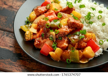 Pineapple and Chicken in sweet and sour sauce with bell pepper, rice and spring onion in black plate Photo stock ©