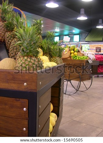 Pineapple basket in a Hypermarket, with a background of vegetables in exhibition.