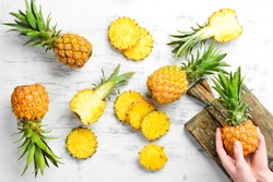 Pineapple collection. Whole and sliced pineapple, on a white wooden background. Top view. Free space for text.