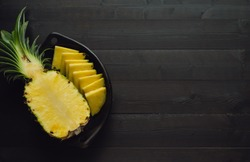 Pineapple cut in black ceramic bowl on black wooden background. Copy space. Top view.
