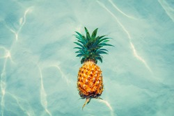Pineapple into water on sunny beach
