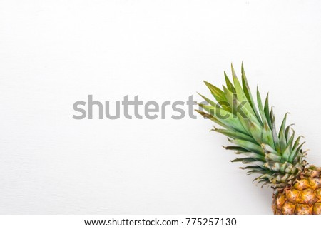 Pineapple on a wooden background. Top view. Free space for text. #775257130