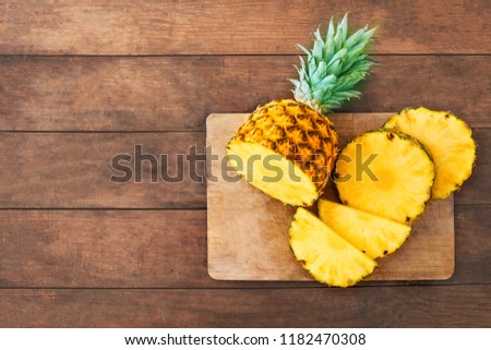 Pineapple on wood texture background. Whole and sliced tropical pineapple on wooden cutting board  with copy space. Top view
