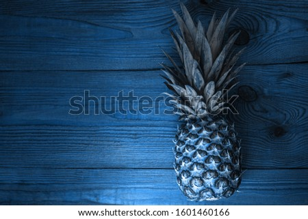 Pineapple on wooden background flatlay in trendy blue toning. tlTropical fruits, diet, slimming vegan foods, weight loss. Minimal photo, top view, trendy social media banner.Creative minimalism style.