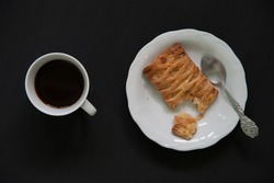 Pineapple pie with bite and hot black coffee on dark background