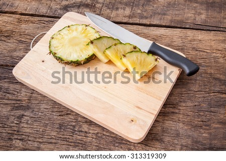 pineapple slice and knife on wooden cutting board, on wooden table top