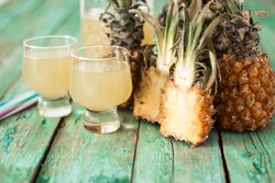 Pineapple slices and juice in glassware on wooden table, healthy detox food