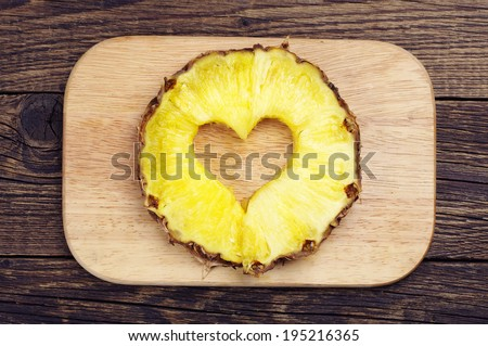 Pineapple slices with a cut in the shape of hearts on a cutting board
