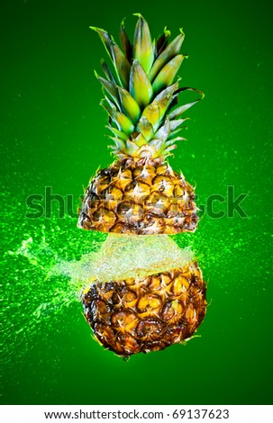 Pineapple splashed with water on a green background