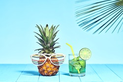 Pineapple, tropical fashion on Beach. Minimal concept. Bright summer vibes, hipster pineapple. Creative art vacation concept. Summertime hot cocktail party, funny pineapple