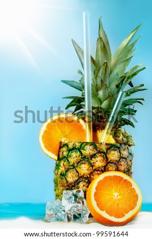 Pineapple with oranges and tubules on white beach sand. Fresh cold drink