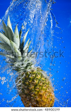 Pineapple with splashing water on blue background