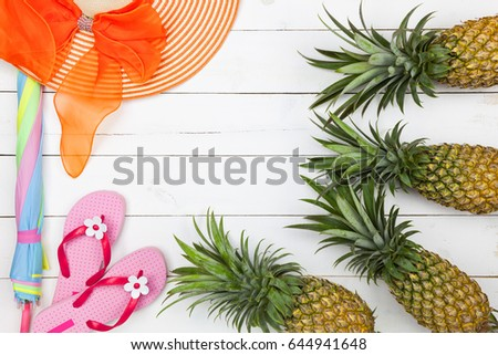pineapple with summer accessory on white wooden background #644941648
