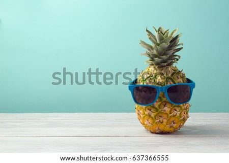 Pineapple with sunglasses on wooden table over mint background. Tropical summer vacation and beach party concept.