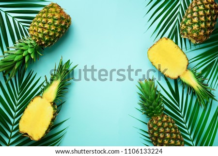Pineapples and tropical palm leaves on punchy pastel turquoise background. Summer concept. Creative flat lay with copy space. Top view.