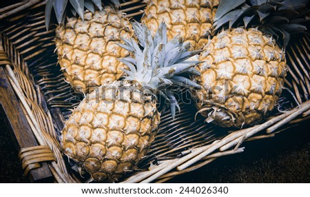 Pineapples in wicker basket at organic farmers market in Paris (France). Aged photo. #244026340