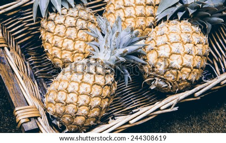 Pineapples in wicker basket at organic farmers market in Paris (France). Aged photo. #244308619