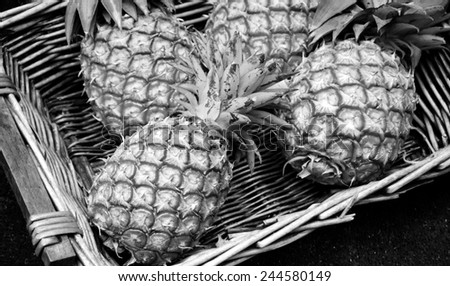 Pineapples in wicker basket at organic farmers market in Paris (France). Aged photo. Black and white. #244580149