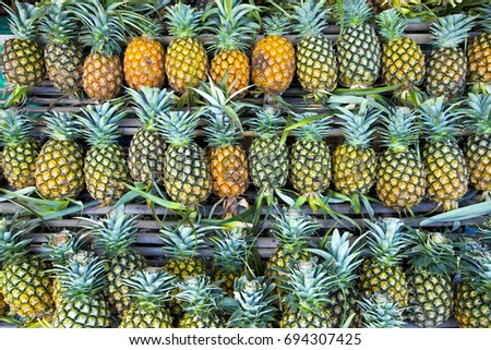 Pineapples on the shelf. It is one of the famous fruit in southeast Asia can be use as background of fruit and fruit juice or nature background.