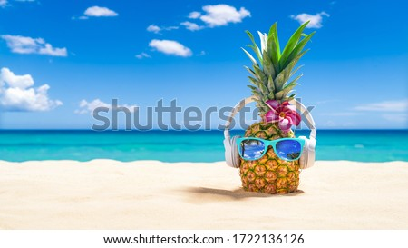 PinePineapple with sunglasses and headphones at tropical beach - Holiday Vacation Concept