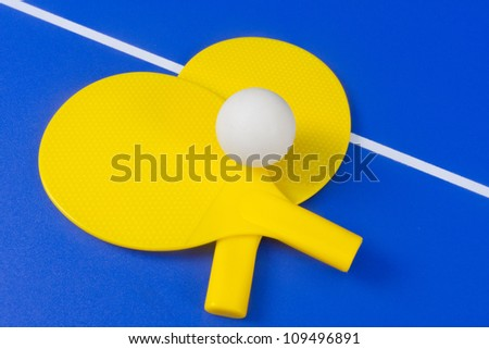Ping Pong ball and paddles on game table