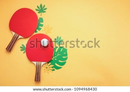 Ping pong rackets and ball with tropical leaves. Summer sports and recreation flat lay on a sunny yellow background with copy space.