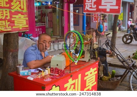 PINGYAO, CHINA, AUGUST 22, 2013: Man is selling locks and chains on the street of pingyao in china,