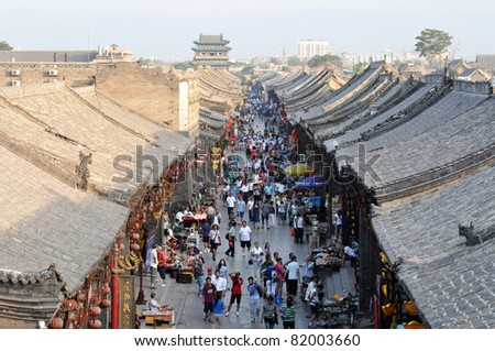 PINGYAO - OCTOBER 1: crowds of people travel during National Day holiday on October 1, 2010 in Pingyao, China. At this time tourist sites are overcrowded with people, like here in old town of Pingyao - stock photo