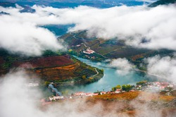 Pinhao village in Douro river valley in Portugal. Vineyards on the mountains in misty morning. Top view. Portuguese wine region. Beautiful autumn landscape.