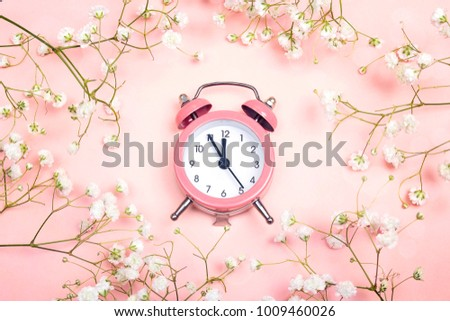 Stock Photo Pink alarm clock and delicate little white flowers on pink background. Top view. Time for love and greetings.