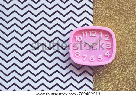 Pink alarm clock on golden and chevron  background #789409513