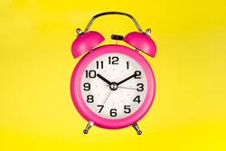 Pink  alarm clock on yellow background.  Pink clock hanging in air