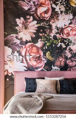 Pink and black pillows on bed against flowers wallpaper in overwhelming bedroom interior. Real photo