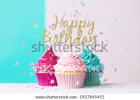 Pink and blue birthday cupcakes with happy birthday sign and confetti