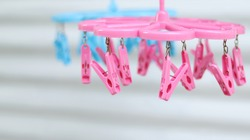 Pink and Blue plastic clothespins, clip clothes on the hangers, use for hanging clothes or underwear after washing and drying. Thailand useful object style, isolated in white zinc blurred background.