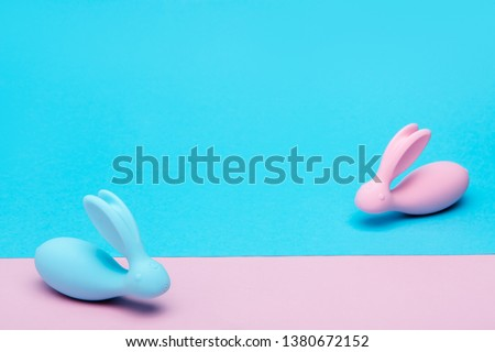Pink and blue rabbits vibrators on blue and pink background. Easter concept for sex shop. Vaginal dildo for girls in the shape of rabbit ears. Easter bunnys. Sex toys. Space for text.