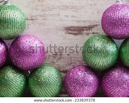 Pink and green christmas balls in a stack over wooden background in a studio shot