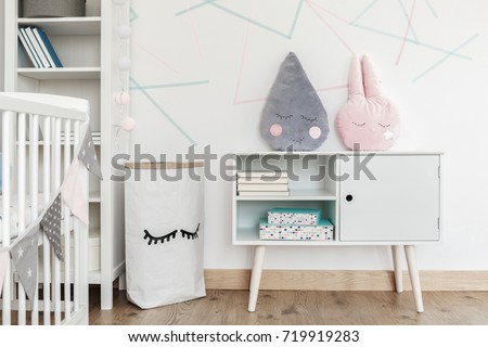Pink and grey pillow on white cupboard in kid's room with paper bag and shelf against triangles wall