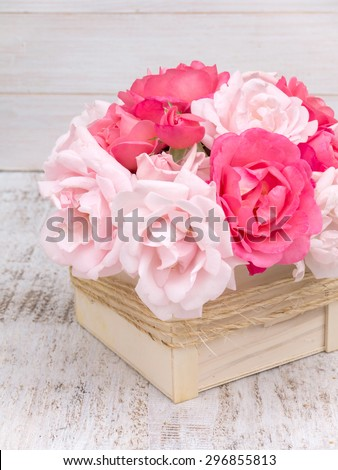 Pink and pale pink roses bouquet in the wooden box tied with jute rope