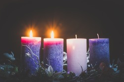pink and purple candles in advent wreath decoration on black background