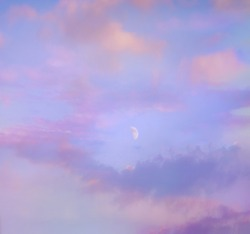 Pink and purple sunset clouds sky with first quarter new moon in the center. Dream magic evening sky with first quarter mystic moon and clouds. Young moon. Blue hours sky