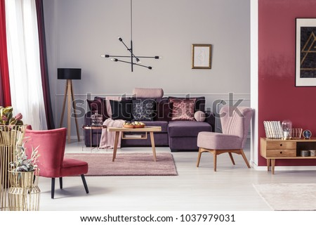 Pink and red armchair in warm living room interior with pillows on settee against the wall with poster