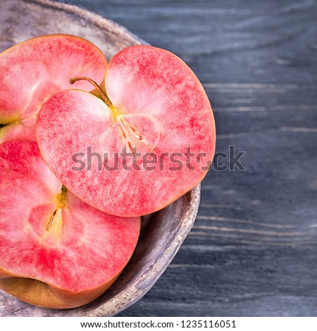Pink and red fleshed apples on a gray background. Apples with pink flesh