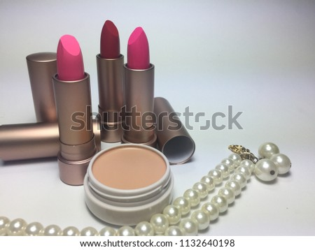 Pink and red moisturizer lipstick in pearl gold package put near powder foundation and pearl necklace on white background