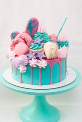 Pink and turquoise cake decorated with macaroons, cupcakes, cake pops, meringues, popsicles and melted chocolate. Turquoise cakestand, white background.