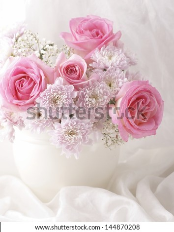 Pink and white flowers in a vase with white decorative fabric