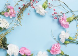 pink and white flowers together with ornamental plants form a composition on a blue background. copy space. flat lay.