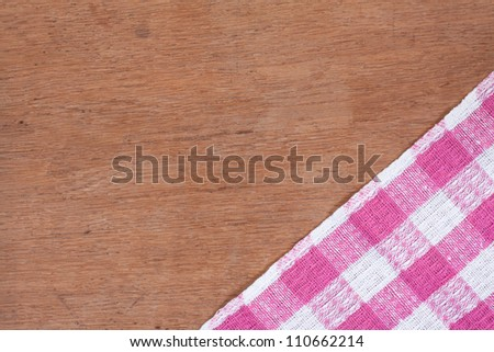Pink and white kitchen textile texture on wood background