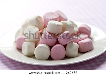 Pink and white marshmallows on a white plate